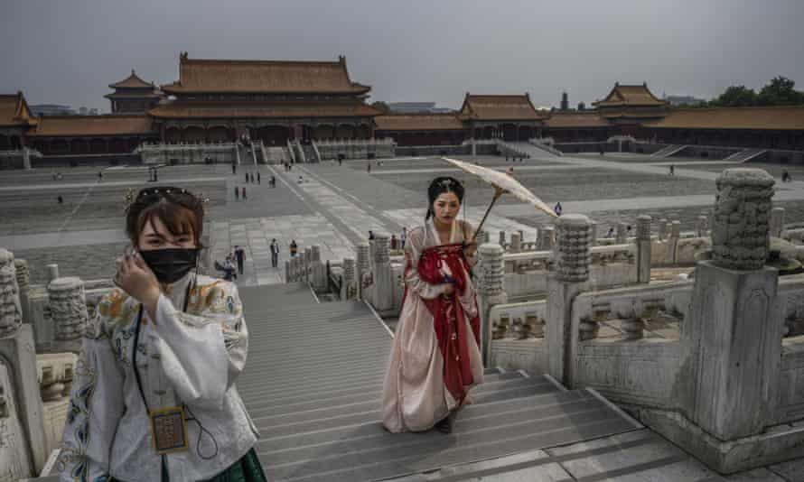 Chinese women dressed in traditional costume known as Hanfu tour the Forbidden City in Beijing