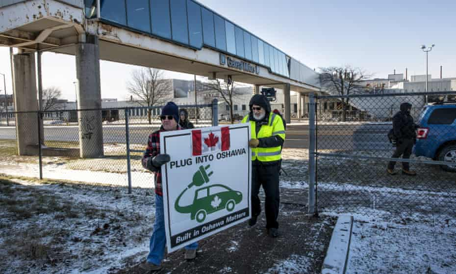 Activists hold a sign outside the GM plant in Oshawa, Ontario, on the final day of production on 18 December. More than 2,700 jobs at the company will disappear, as well has thousands of others tied to supply chains.
