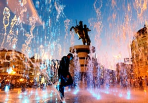 """Skopje, North MacedoniaPeople play with water from a fountain near the """"Warrior on a horse"""" monument"""