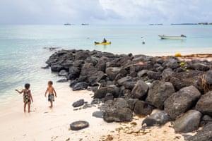 Children play near beach defences along the beach in the Funafuti lagoon