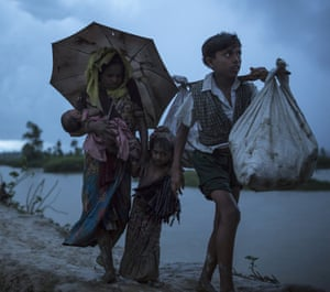 Rohingya refugees walk across Paddy fields in the pouring rain at dusk