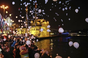 People release balloons and lanterns in Istanbul's Ortakoy district, by the Bosphorus