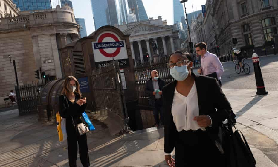 Workers in face masks make their way down streets near the Bank of England in London
