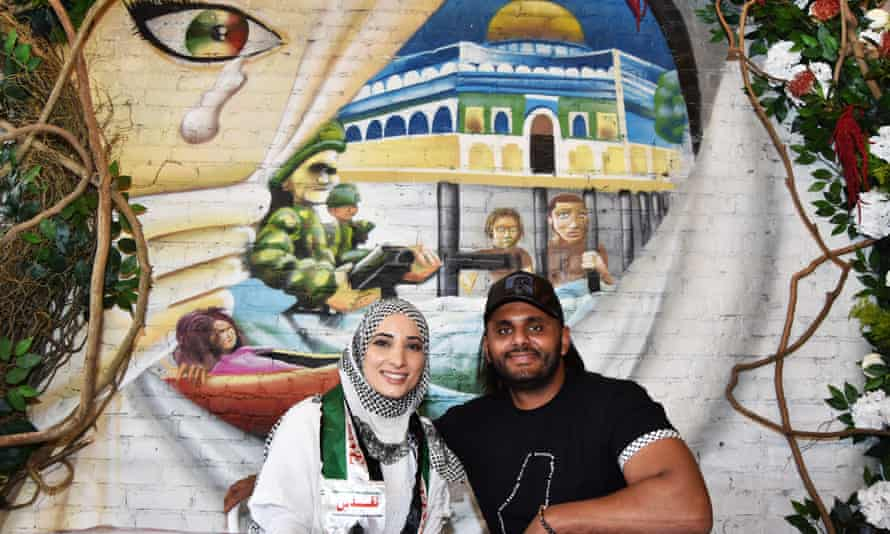 Ayat Masoud and Abdul Elenani sit in front of a mural in Ayat NYC, their Palestinian restaurant in Bay Ridge, Brooklyn.