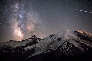 Ascent of Angels. A meteor can be seen piercing through the darkness as the Milky Way towers above the 4,392m peak of Mount Rainier in Washington, USA. The white lights dotted across the rocky paths of the mountain's face are the headlamps of hikers ascending to the peak