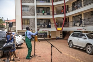 Reverend Paul Machira preaches and sings to residents in an apartment complex in Nairobi, Kenya.