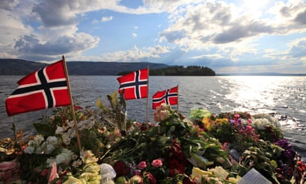 Norwegian flags and flowers are seen close to Utøya island.