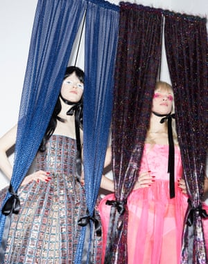 Two models wearing Matty Bovan designs pose between curtains at London Fashion Week autumn/winter 2020 catwalk collections.