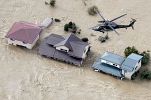 An aerial view shows a Japan Self-Defence Force helicopter flying over residential areas flooded by the Chikuma river following Typhoon Hagibis in Nagano, central Japan, October 13.