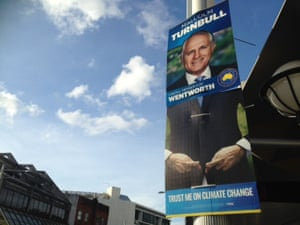 GetUp volunteers in Malcom Turnbull's electorate of Wentworth have added to his official campaign signs to make it appear he is crossing his fingers on climate change.