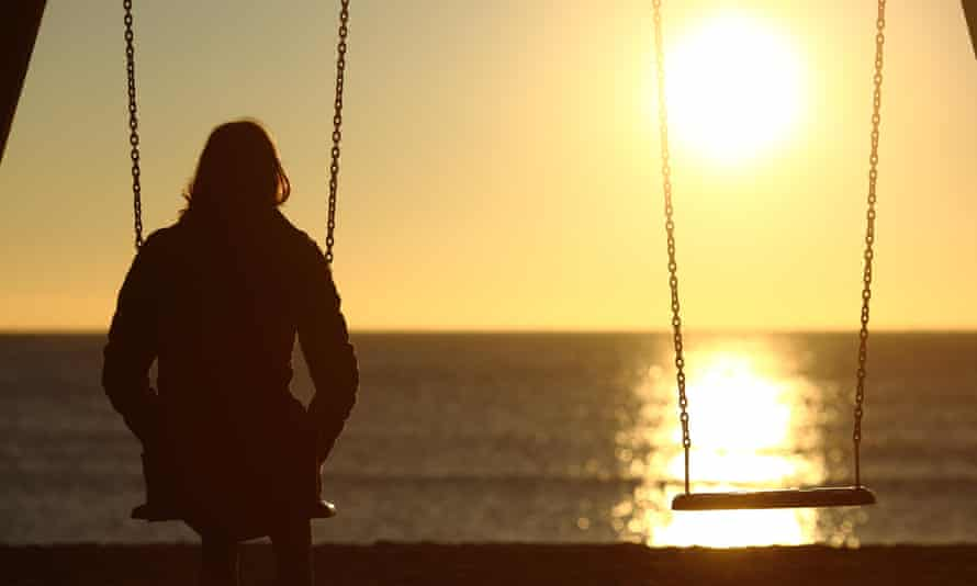 Lonely woman watching sunset alone in winter on the beach