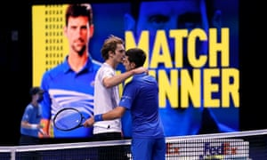 Novak Djokovic (right) embraces Alexander Zverev at the net after beating him in straight sets.