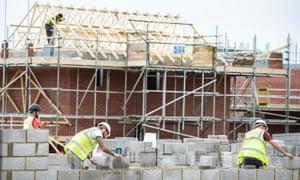 Builders lay blocks on a building site near Bristol.