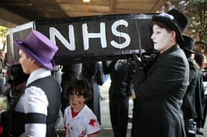 Protesters carry a mock-up of a coffin with the letters NHS on the side