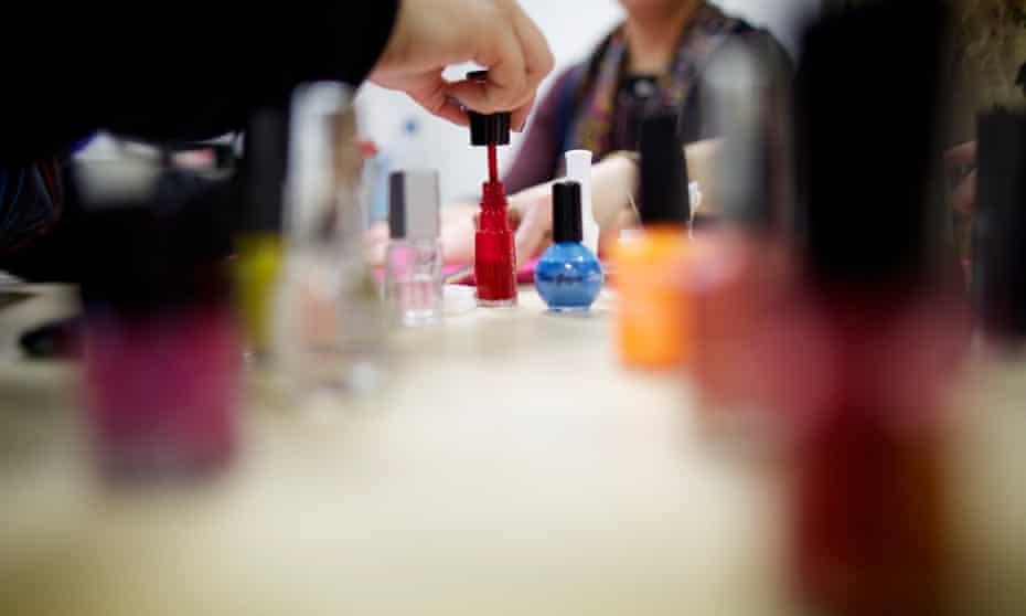 pots of nail varnish with worker and customer in a UK nail bar