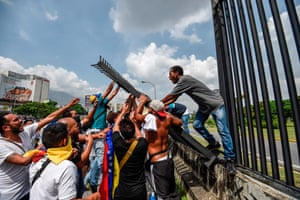 Demonstrators try to tear down a fence at La Carlota airbase