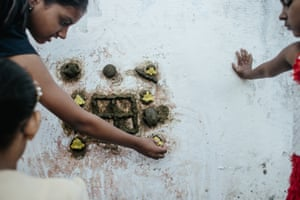 At the entrance of their homes, girls in Piplantri make patterns with flowers.