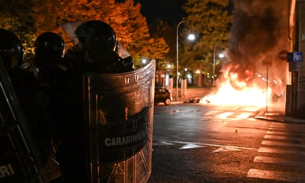 Police officers stand guard as protesters set fire to public property during an anti government demonstration in Turin, Italy.