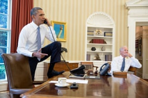 Barack Obama rests a foot on his desk during a phone call as Joe Biden listens in