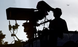 A camera operator at a football stadium