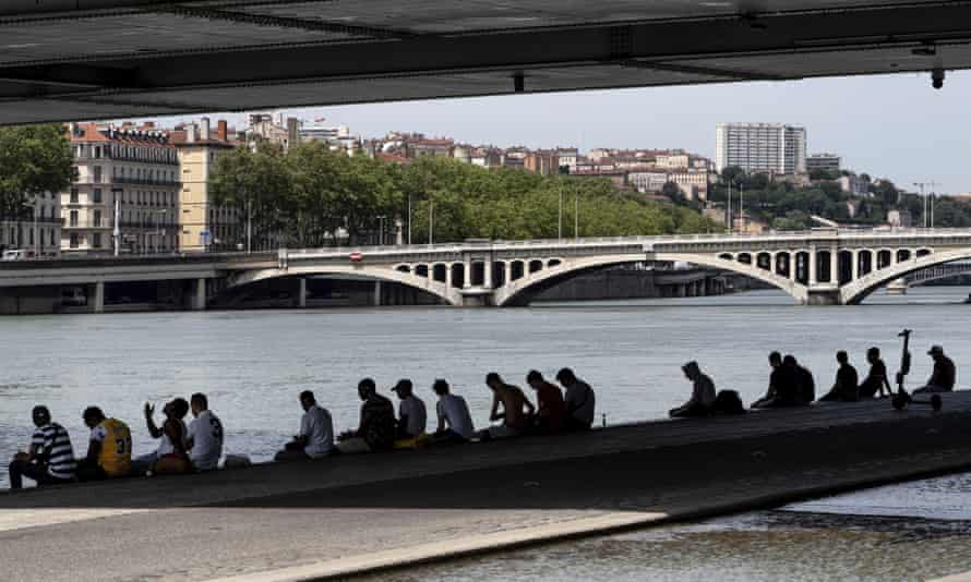 People sit in the shade under a bridge in the center of Lyon, central France. More than half of France was placed on an orange alert for intense heat Monday _ the second-highest level on the scale.