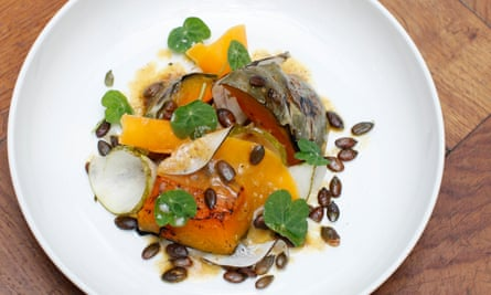 Plate of chunks and curls of pumpkin, with radish and pear, sprinkled with pumpkin seeds