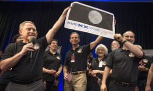 New Horizons principal investigator Alan Stern, left, Johns Hopkins University applied physics laboratory director Ralph Semmel, centre, and New Horizons co-investigator Will Grundy hold a print of a US stamp with their suggested update. At center right under the stamp is Annette Tombaugh, daughter of Pluto's discoverer, Clyde Tombaugh.