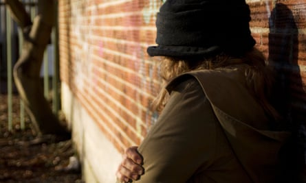 Rear view of a woman standing against a brick wall