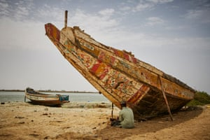 Daoud Diallo sits under the bow of a boat