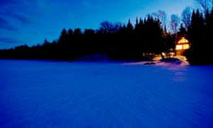 The lights of a lakeside cabin glow on a clear night.