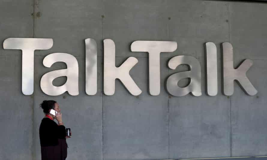 A woman speaks on her phone as she passes a branded logo outside the Talktalk headquarters in London