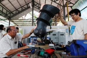 Engineer Boonyu Thippaya, left, and a member of his team adjust a prosthetic leg for Mosha's friend Motola