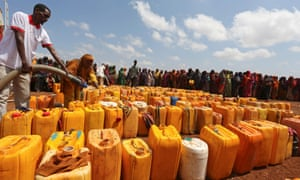 Internally displaced Somali women gather with their jerrycans to receive water