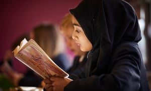 Schoolgirl in headscarf reading book