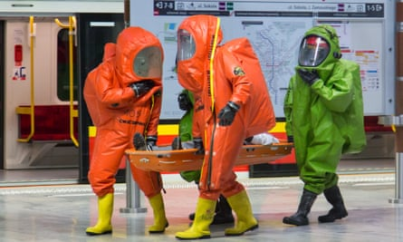 emergency officers in orange and green protective suits and gas masks during a counter-terrorism exercise on the metro in Warsaw, Poland