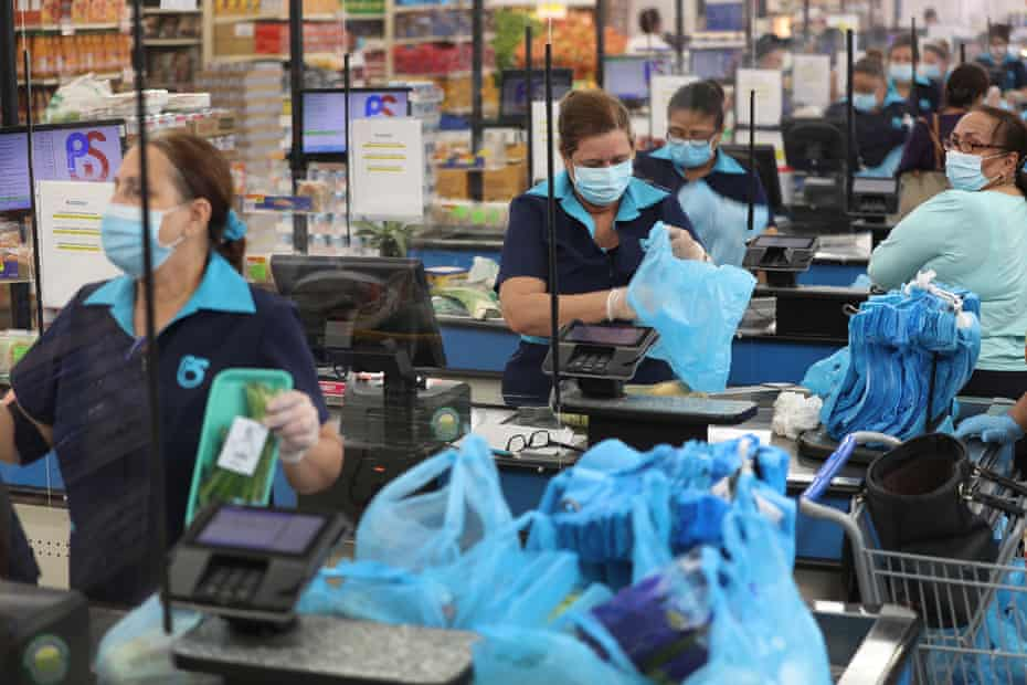 Diana Rivero stands behind a partial protective plastic screen and wears a mask and gloves as she works as a cashier at the Presidente Supermarket on April 13, 2020 in Miami, Florida. The employees at Presidente Supermarket, like the rest of America's grocery store workers, are on the front lines of the coronavirus pandemic, helping to keep the nation's residents fed.