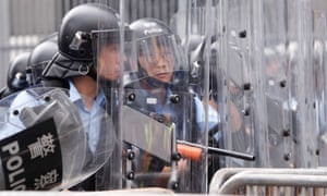 Police officers stand behind riot shields during a demonstration against a proposed extradition bill.