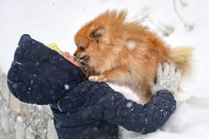 A woman plays with a dog during a snowstorm in Vladivostok, Russia
