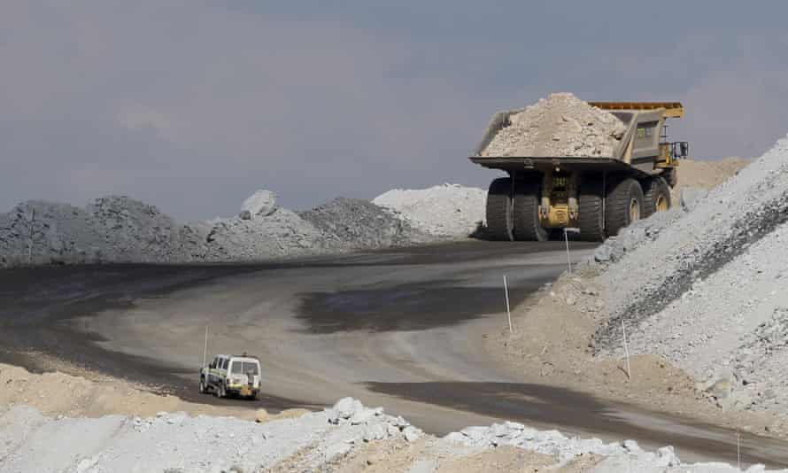 Four-wheel-drive vehicle follows a large mining truck as it makes its way to the top of a coalmine