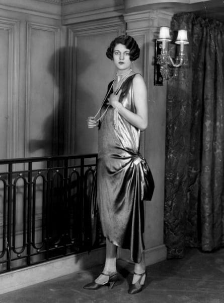 A woman wearing a fashionable dress by Erté and a long string of beads, March 1927.