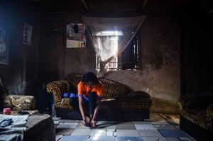 Rita Okoh, 21, ties her shoelace in her family house as she prepares for soccer training in Abuja, Nigeria