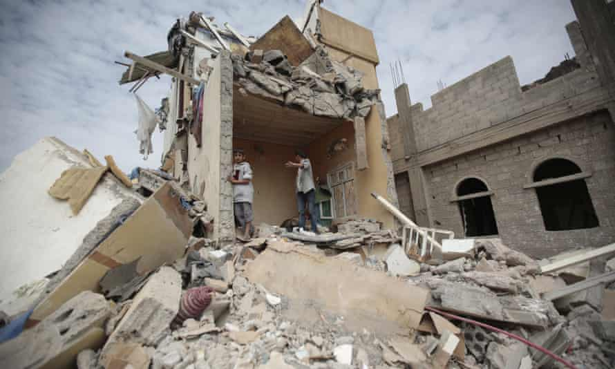 Boys stand on the rubble of a house destroyed by Saudi-led airstrikes in Sana'a, Yemen.