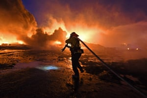 A firefighter drags a hose closer to battle a grass fire in Knightsen, California.