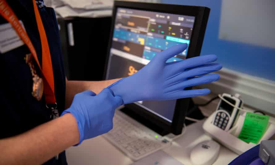An NHS consultant puts on gloves