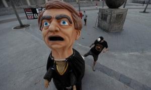 A man kicks a huge effigy of president Jair Bolsonaro during a protest in Rio de Janeiro.
