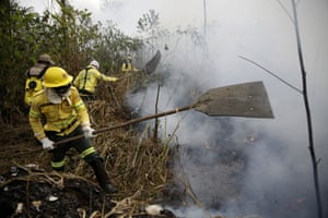Firefighters work to put out fires along the road to Jacunda National Forest, near the city of Porto Velho in the Vila Nova Samuel region which is part of Brazil's Amazon, Monday, Aug. 26, 2019.