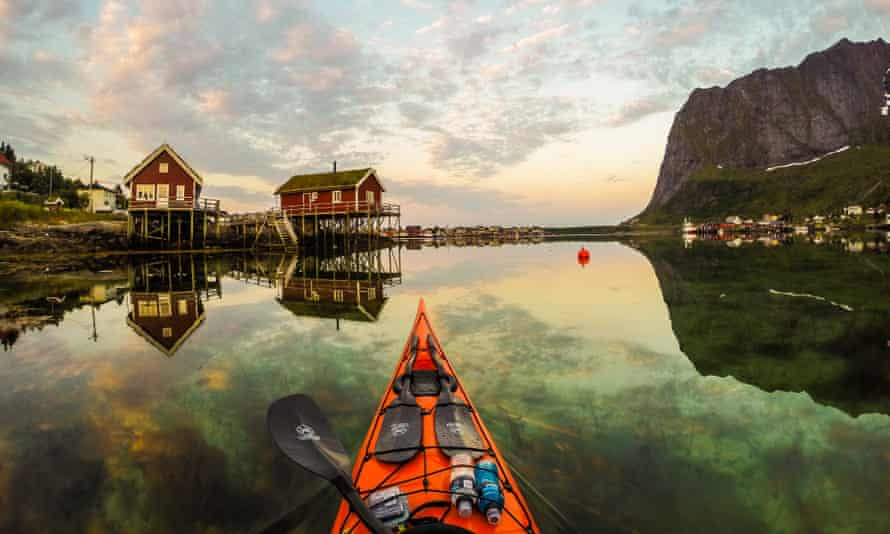 A photographer takes images of Norway from a kayak.