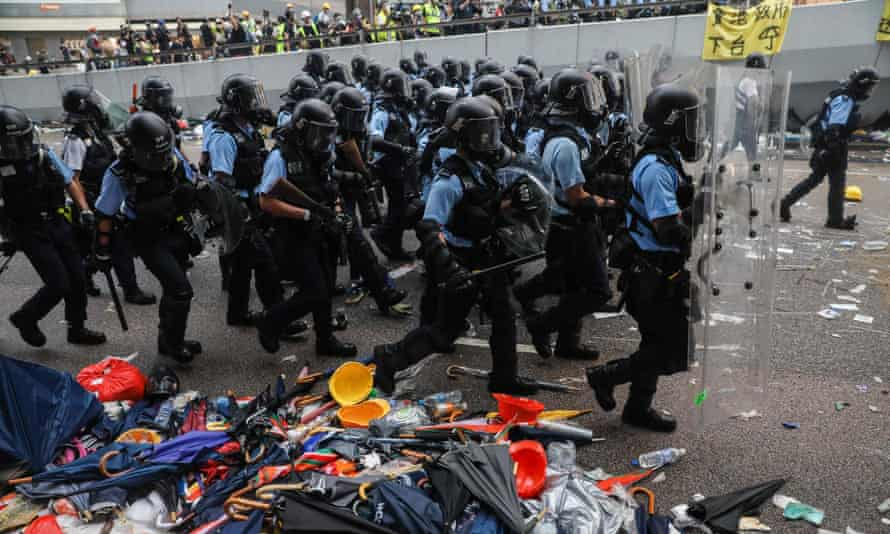 Police advance towards protesters during a rally.