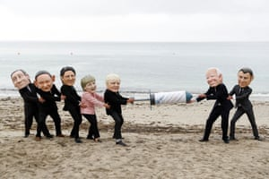 Oxfam activists wearing caricatures of G7 leaders protest on a beach near Falmouth