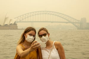 German tourists Julia Wasmiller and Jessica Pryor take a selfie at Mrs Macquarie's chair, wearing face masks due to heavy smoke on 19 December.